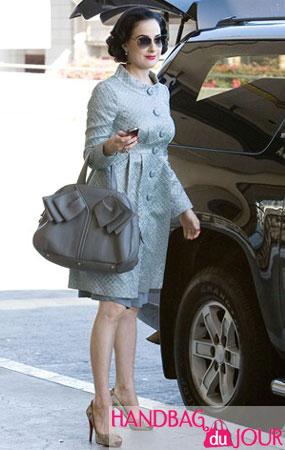 Dita von Teese with the YSL obi large stone handbag