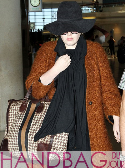 British singer Adele-with-the-Gucci-'seventies'-large-Houndstooth tote-with-signature-web in London Heathrow airport