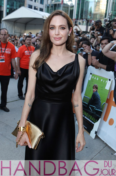 Actress Angelina Jolie's gold $15,000 Louis Vuitton Lockit PM Devotion handcuff clutch handbag at Moneyball premiere at the 2011 Toronto International Film Festival in Toronto, Canada