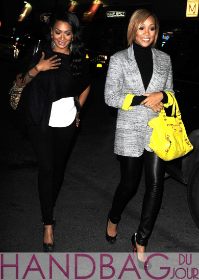 Lala Anthony and Monica Brown wearing a Diane von Furstenberg Vincent Lacquered Tweed Blazer with citron accents, a black turtleneck and skinny leather pants, Christian Louboutin Asteroid Pumps in black and a bright yellow Balenciaga Giant Bag with gold hardware
